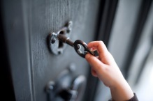 Hand of a young boy unlocking a door using a large old-fashioned metal key conceptual of security, ownership and opportunity